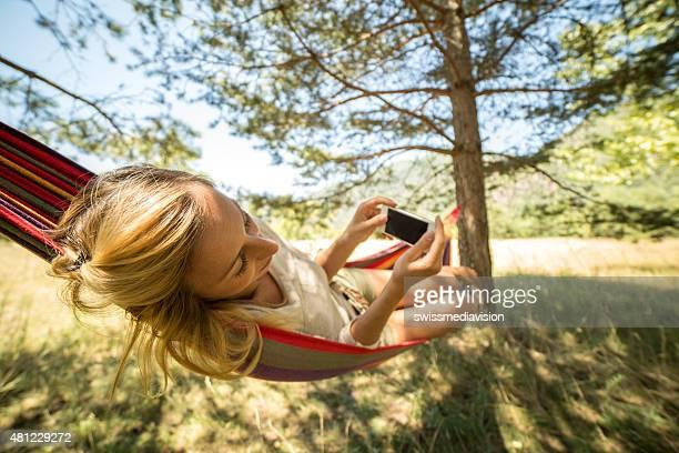 Jeune femme sur hamac à l'aide de téléphone mobile