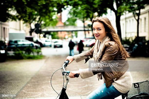 young woman on her bicycle looking at camera - alleen één jonge vrouw stockfoto's en -beelden