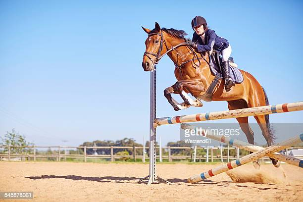 Young woman on horse crossing obstacle on course