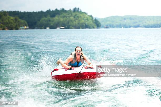 young woman on inflatable raft pulled by speedboat in lake blue ridge - inflatable ring stock pictures, royalty-free photos & images
