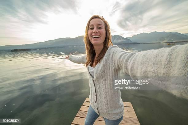 young woman on jetty above lake, takes selfie portrait - groothoek stockfoto's en -beelden