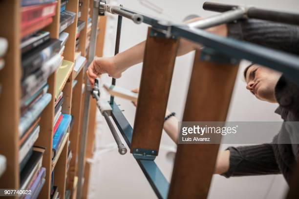 Young woman on ladder choosing book from shelf