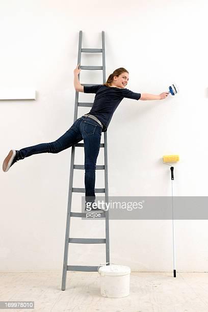 Jeune femme sur le mur de peinture échelle blanc