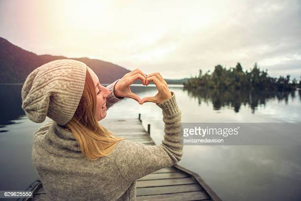 young woman on lake pier, makes heart shape finger frame - alles hinter sich lassen stock-fotos und bilder