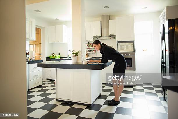 young woman on laptop in kitchen - bending over in skirt stock pictures, royalty-free photos & images