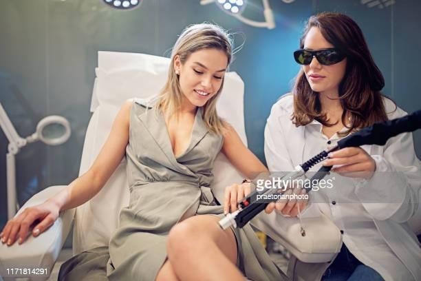 mujer joven en el procedimiento de depilación láser - depilacion laser fotografías e imágenes de stock