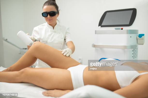 young woman on laser hair removal treatment - medical laser stock photos and pictures
