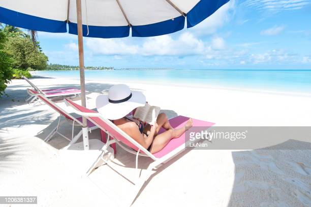 young woman on lounge chair reading book under parasol at the tropical beach - liu he stock pictures, royalty-free photos & images