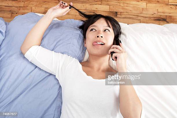 Young woman on mobile phone lying on bed, head and shoulders, overhead view