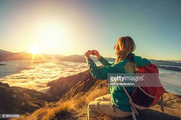 Young woman on mountain top photographing spectacular landscape