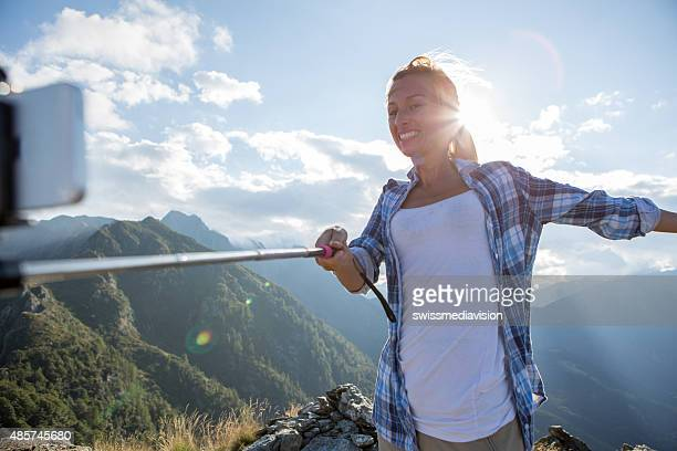 Young woman on mountain top taking selfie using mobile phone