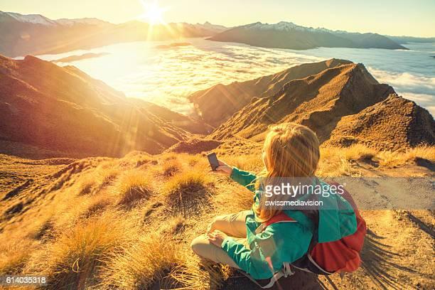 young woman on mountain top text messaging on mobile phone - wanaka - fotografias e filmes do acervo