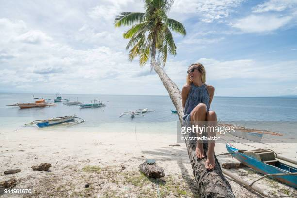 young woman on palm tree contemplating paradise - wonderlust stock pictures, royalty-free photos & images
