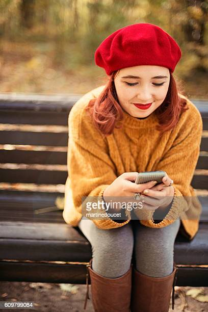 "young woman on park bench with mobile phone in autumn. - ""martine doucet"" or martinedoucet stock pictures, royalty-free photos & images"