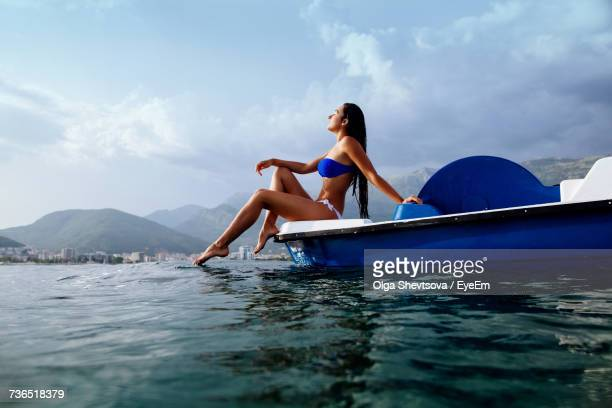 Young Woman On Pedal Boat Against Sky