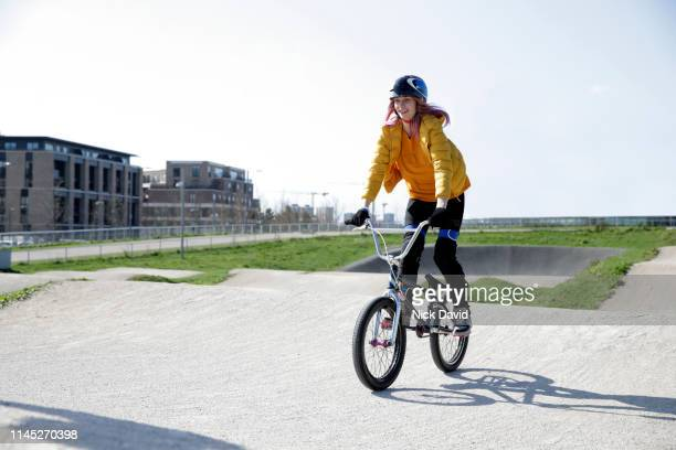 young woman on pedals of bmx on cycle race track - bmx track london stock pictures, royalty-free photos & images