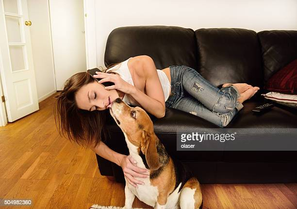 Young woman on phone in sofa, beagle dog