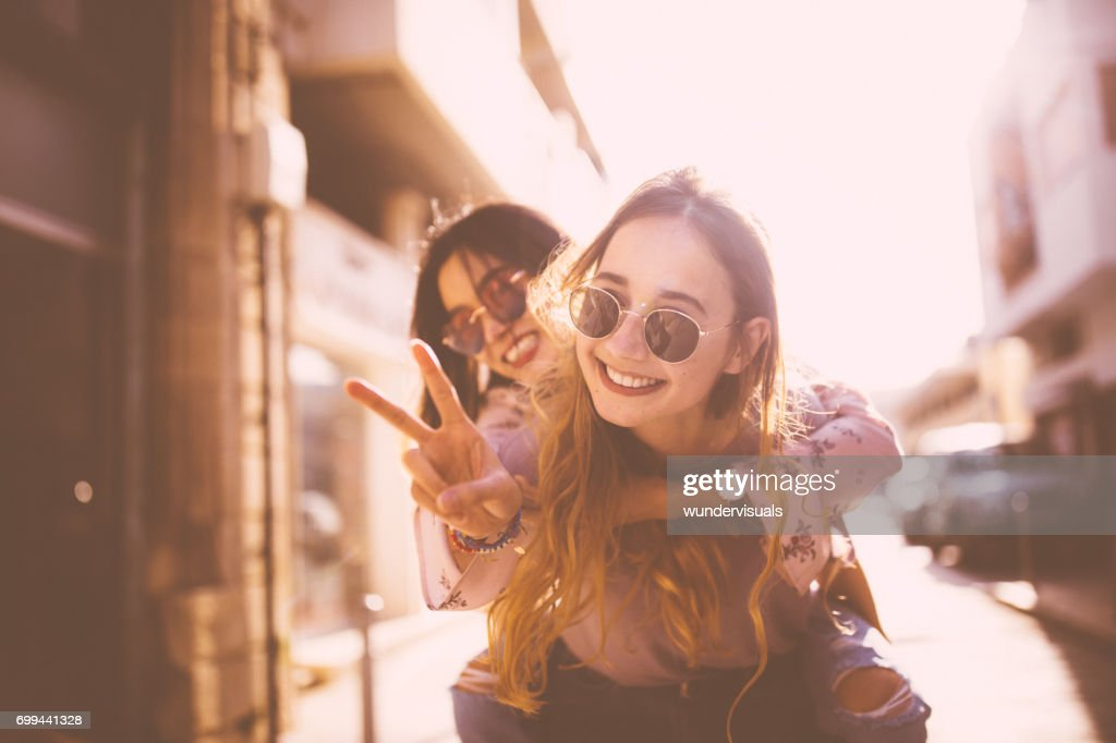 Young woman on piggyback ride doing the peace sign : Stock Photo