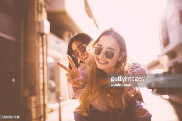 young woman on piggyback ride doing the peace sign - girlfriend stock pictures, royalty-free photos & images