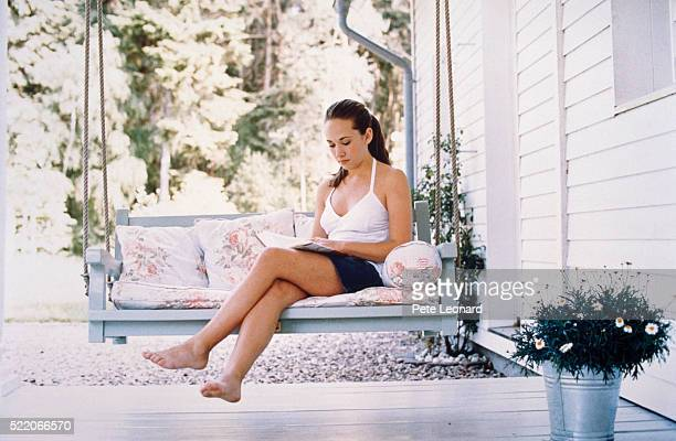 Young Woman on Porch Swing Reading Book