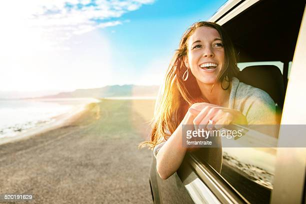 Young woman on road trip looking out the car window