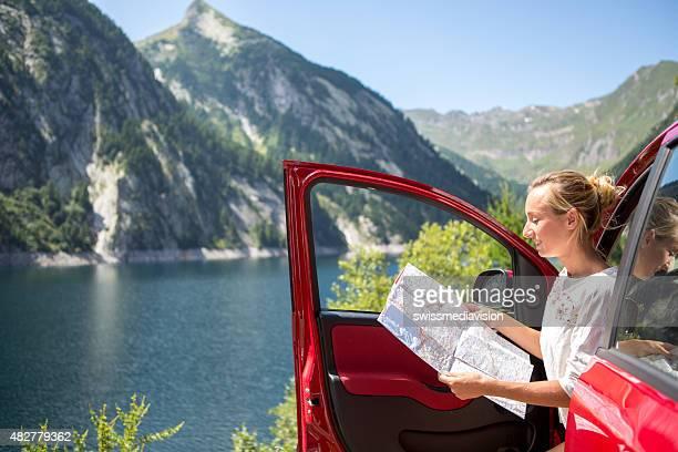 Junge Frauen auf Autoreise-Schweiz lesen Karte für die Anfahrt