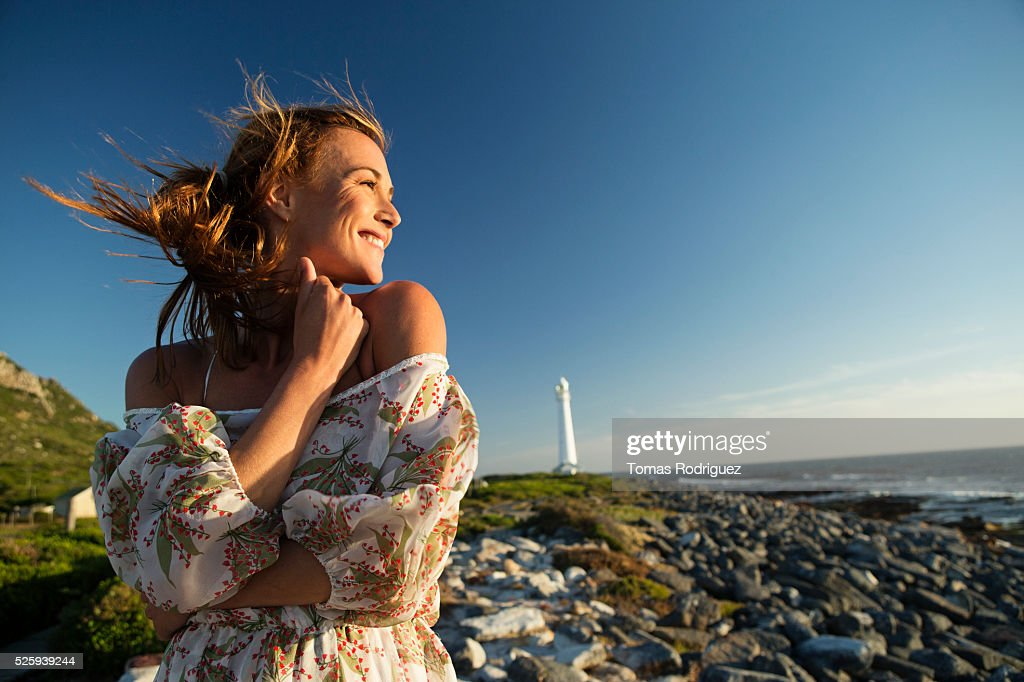 Young woman on rocky beach : Stock Photo