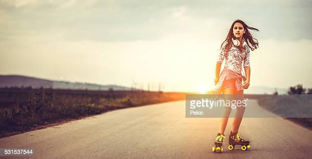 Mujer joven sobre patines de rodillo de patinaje en puesta de sol