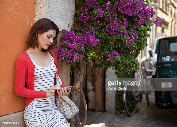 young woman on roman street, using mobile phone - striped dress stock photos and pictures