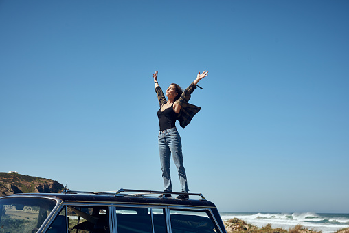 Young woman on roof of car with arms outstretched - gettyimageskorea