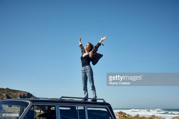 young woman on roof of car with arms outstretched - libertad fotografías e imágenes de stock