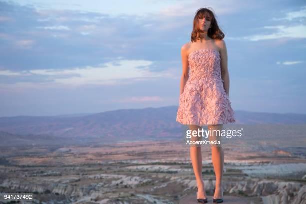 カッパドキアの上のピンクのドレスで屋上で若い女性。 - strapless ストックフォトと画像