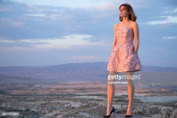 mujer joven en azotea en vestido rosa por encima de capadocia. - aplique arte de la costura fotografías e imágenes de stock