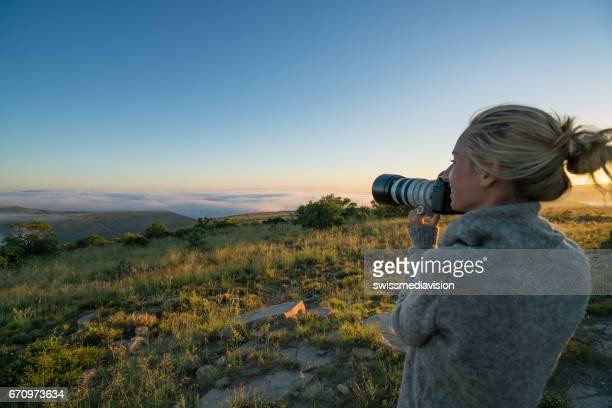 Jonge vrouw op safari landschap fotograferen
