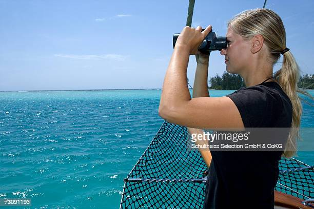 Young woman on sailboat looking through binoculars, side view