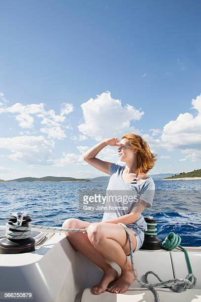 Young woman on sailboat sits looking out to sea