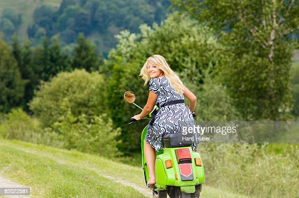 Young woman on scooter, smiling, portrait
