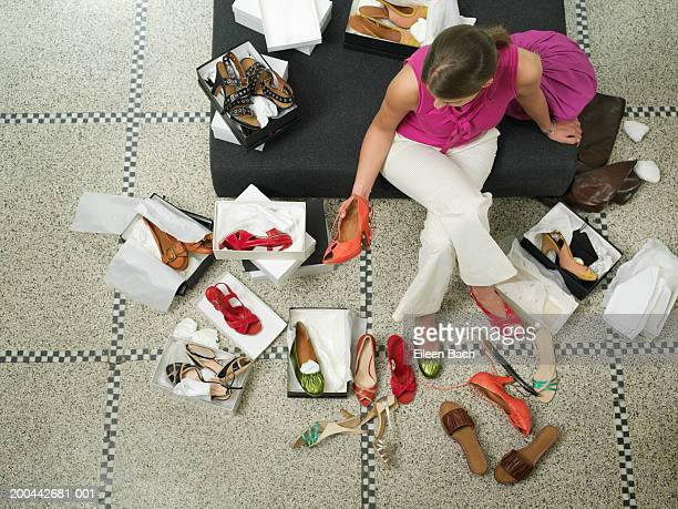 Young woman on seat in shop trying on shoes, overhead view