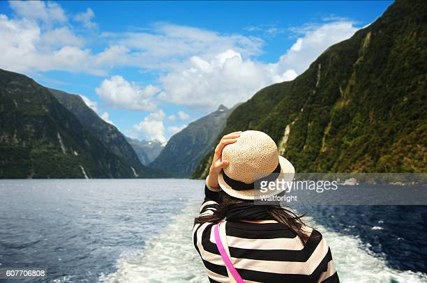 young woman on ship on milford sound cruise. - tourism stock pictures, royalty-free photos & images