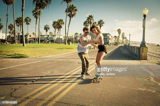 Young woman on skateboard at San Diego beach, boyfriend helping