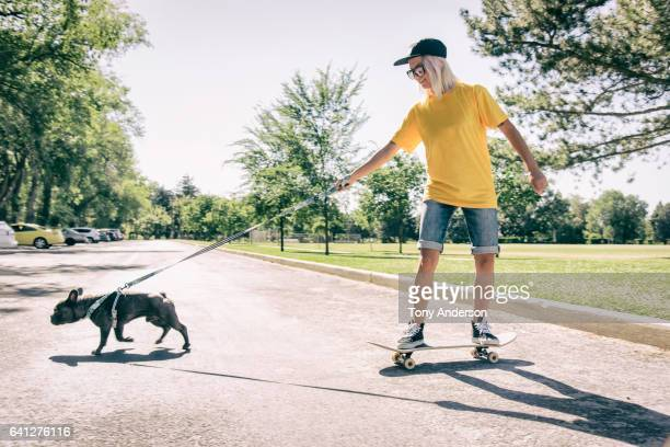 Young woman on skateboard being pulled by her dog