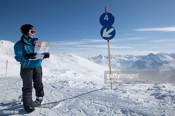 Young woman on snowboard looking at map