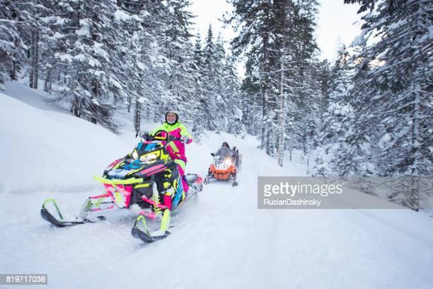jovem mulher na turnê de motas de neve na floresta congelada. - snowmobiling - fotografias e filmes do acervo