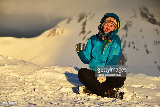 Young woman on snowy mountain at sunrise