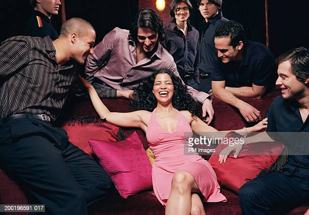 Young woman on sofa in nightclub men looking at her, laughing