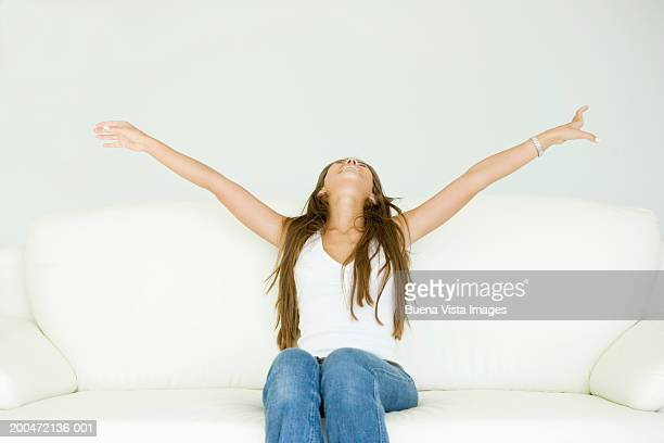 Young woman on sofa spreading arms wide