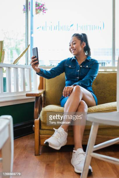 young woman on sofa with phone - mini dress stock pictures, royalty-free photos & images