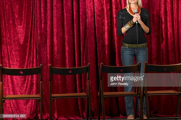Young woman on stage, holding microphone, view over empty seats