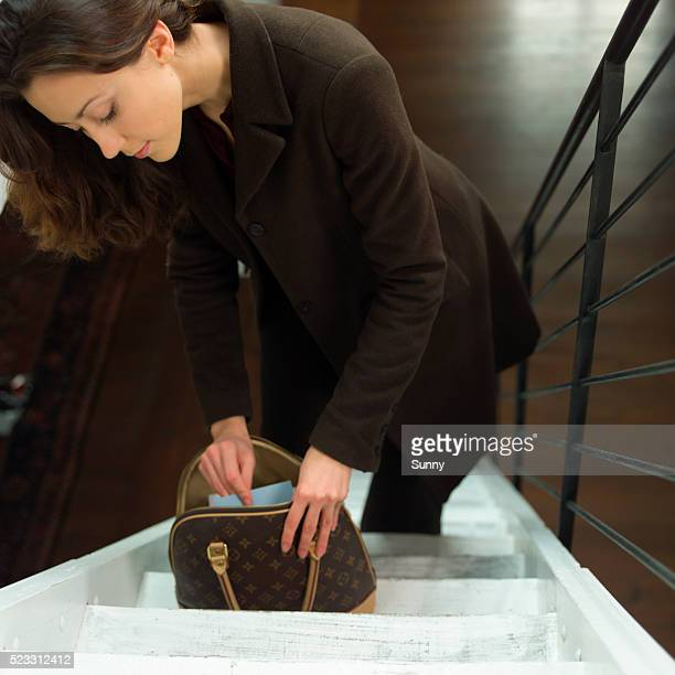 young woman on stairs looking into her handbag - overcoat stock pictures, royalty-free photos & images