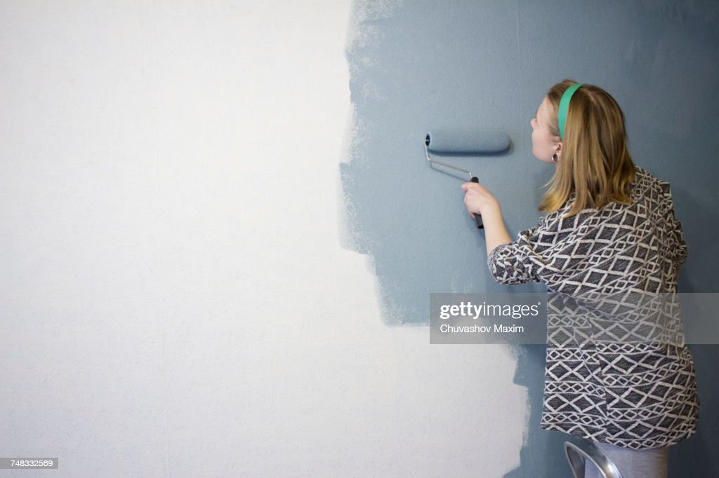 Young woman on step ladder applying grey paint to interior wall at home : Stock Photo